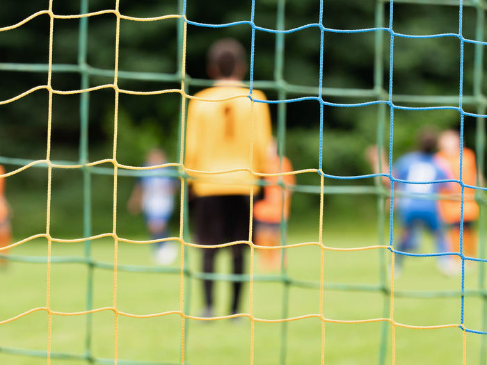 View through soccer gate net. g oalkeeper slowly backs up during the opponents attack. abstract view