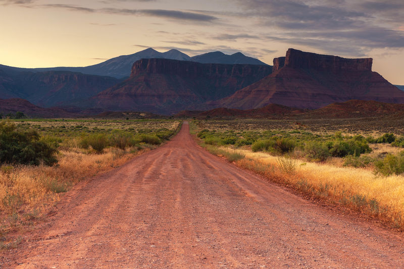 Dirt road along landscape and mountains against sky