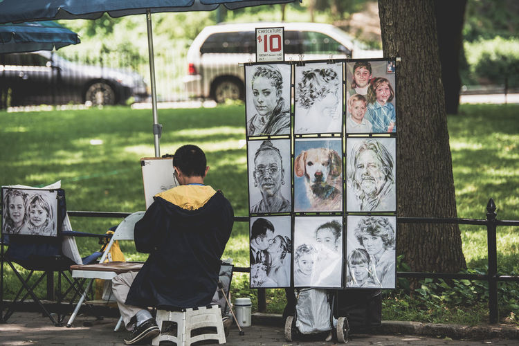 Man Making Sketch Against At Park