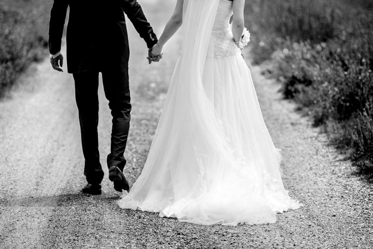 Rear view low section of wedding couple walking on gravel road