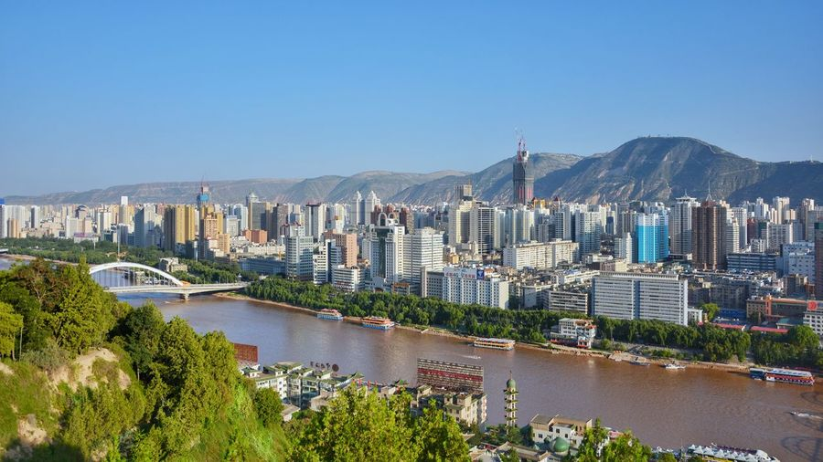 High Angle View Of Cityscape By Yellow River Against Clear Blue Sky
