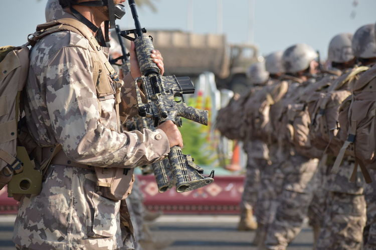 Close-up of army soldiers with rifle on road