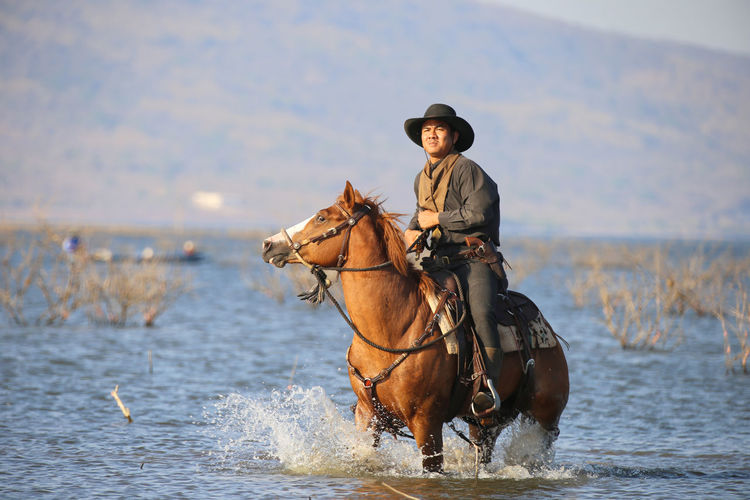 Mammal Water Animal Themes Real People Domestic Animals Domestic Animal One Person Pets Animal Wildlife Hat One Animal Horse Leisure Activity Sea Day Livestock Nature Lifestyles Riding Outdoors Mature Men Cowboy Hat