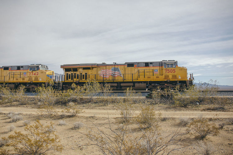 Arid Climate Cloud - Sky Day Freight Train Freight Transportation Grass Land Vehicle Landscape Mode Of Transport Nature No People Outdoors Scenics Sky Train Transportation Tree