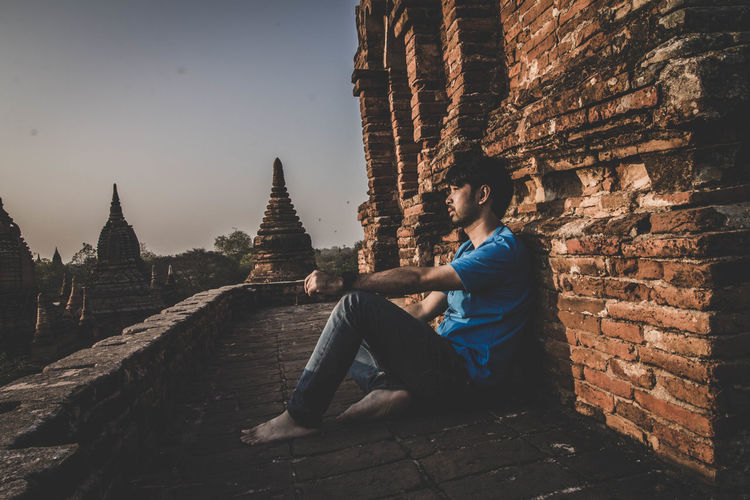 Side view of man sitting outside temple