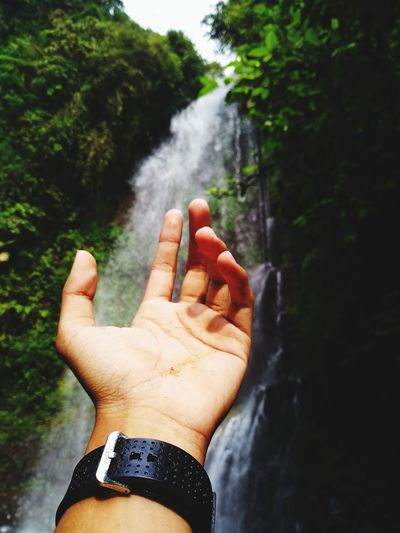 Cropped Image Of Hand Against Waterfall