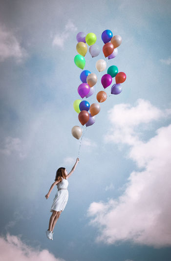 Girl holding bunch of balloons while flying at cloudy sky