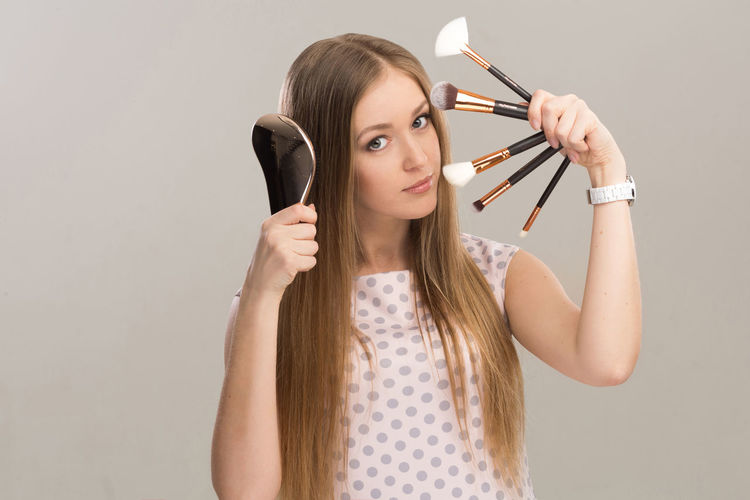 Beautiful Woman Holding Make-Up Brushes While Standing Over Gray Background