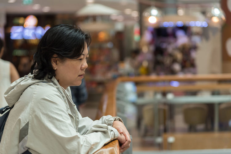 Side View Of Woman Standing By Railing In Shopping Mall
