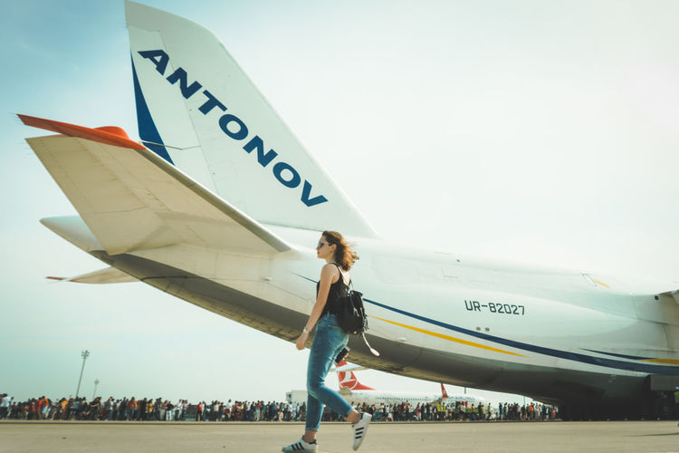 Woman standing on airplane against sky