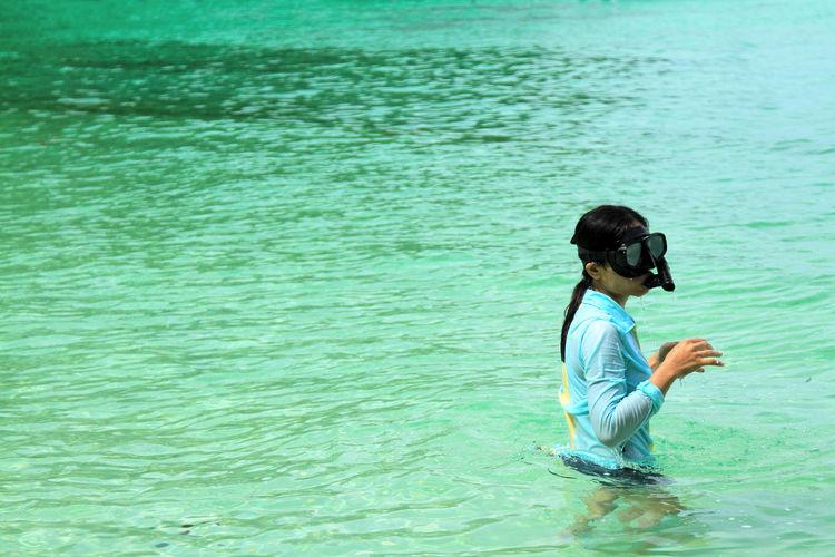 Boy sitting in sea