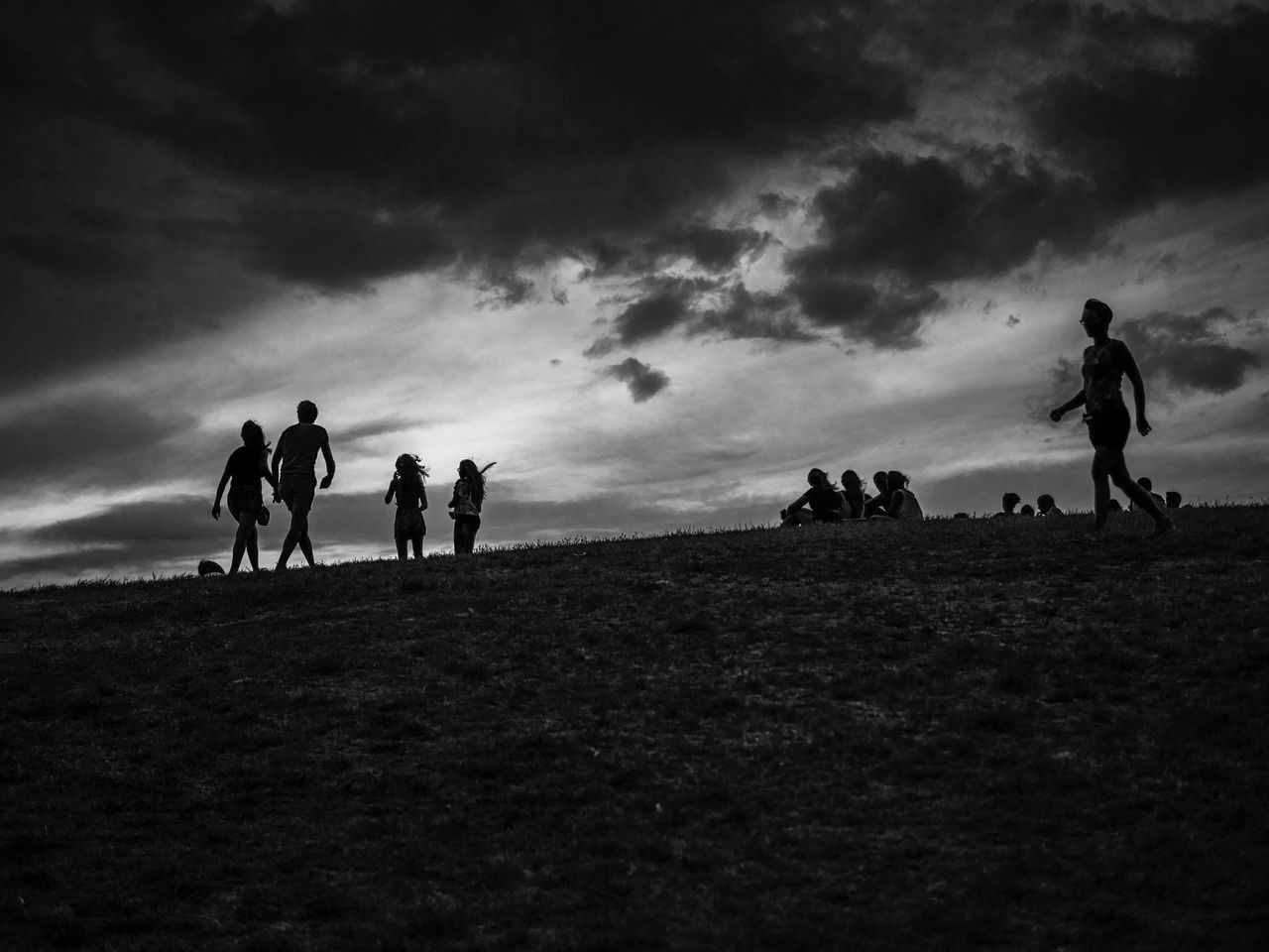 People On Field Against Cloudy Sky