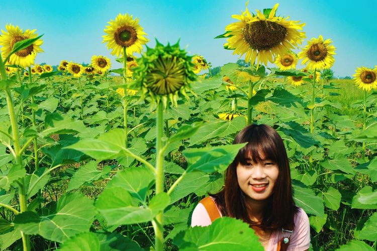Portrait of smiling young woman against plants and sky