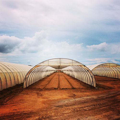Empty Greenhouses Against Cloudy Sky