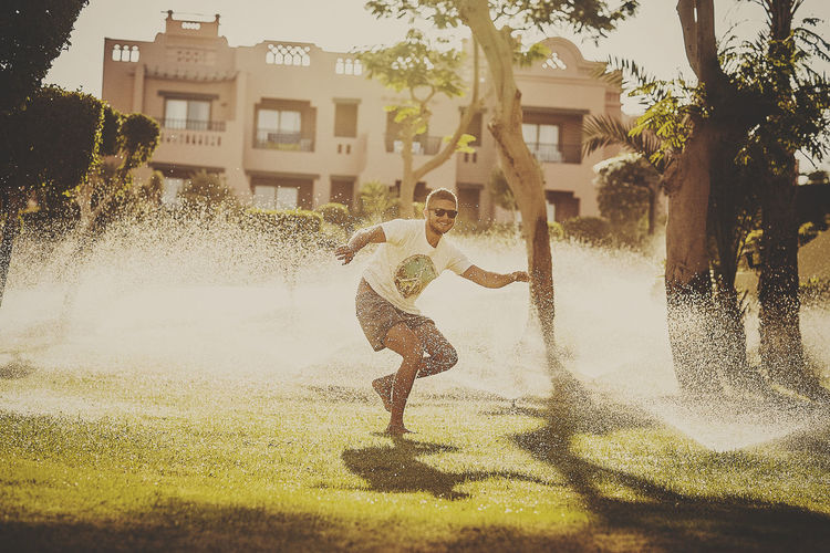 Playful man standing amidst sprinklers in yard