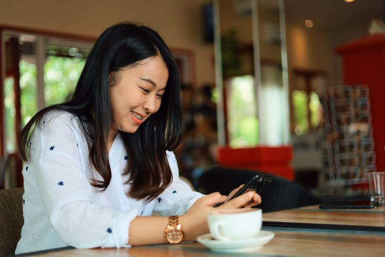 Young Adult One Person Cup Coffee - Drink Sitting Drink Coffee Long Hair Cafe Table Young Women Food And Drink Mug Real People Coffee Cup Lifestyles Hairstyle Smiling Women Leisure Activity Hair Wireless Technology Beautiful Woman