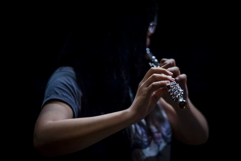 Close-up of person playing flute against black background