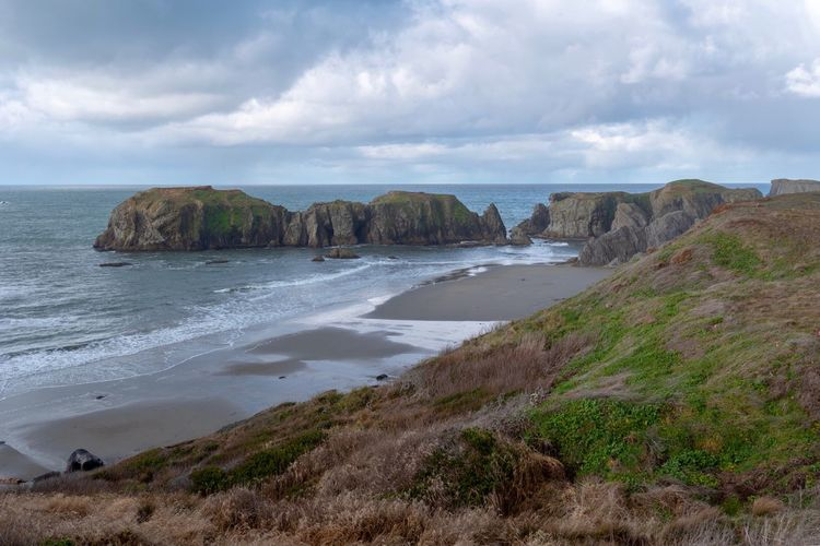 Landscape of rock outcroppings at the Pacific Ocean in Bandon Oregon Seascape Ocean View Bandon, Oregon Rock Formations Oregon Clouds And Sky Water Sky Cloud - Sky Sea Land Beach Scenics - Nature Idyllic Plant Day No People Nature Tranquility Tranquil Scene Beauty In Nature Sand