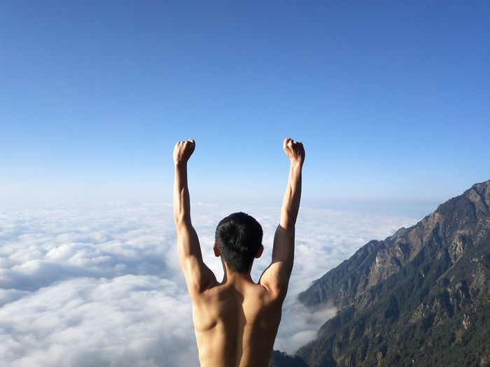 Rear view of shirtless man with arms raised standing against blue sky
