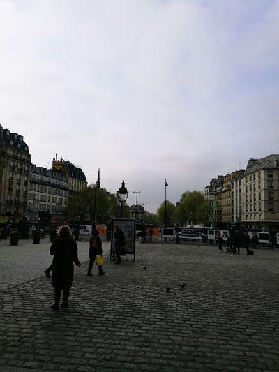 People walking on sidewalk in city against sky