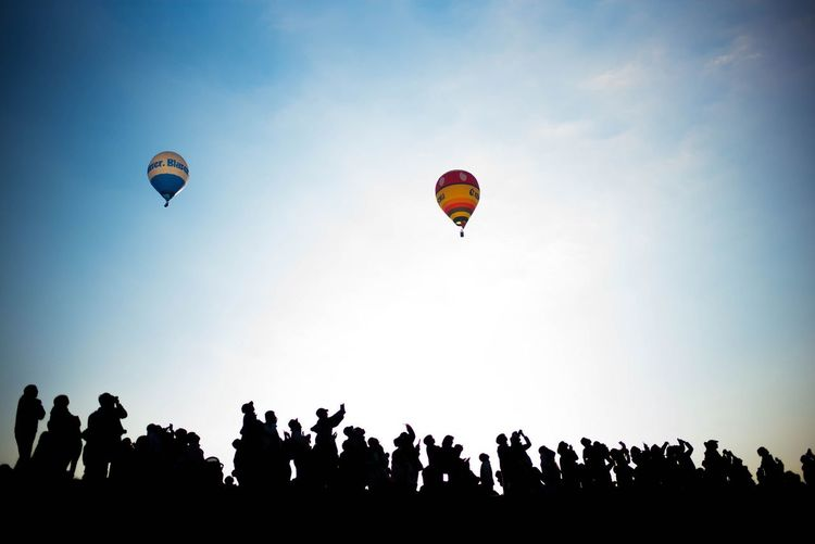 Low angle view of silhouette people flying against clear sky