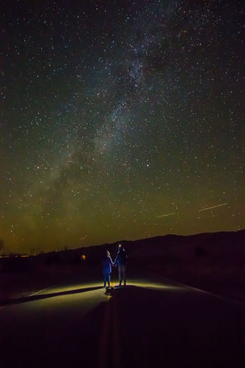 Rear View Of Couple Standing On Road Against Star Field