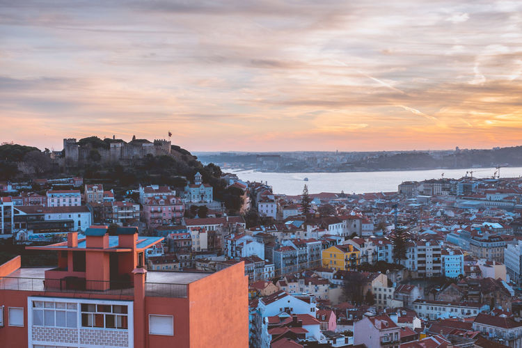 Sunset in Lisbon overlooking the castle Architecture Built Structure Travel Destinations Lisbon Portugal Europe Building Exterior City Building Residential District Sky Crowded Crowd Cloud - Sky Sunset Cityscape High Angle View Nature Town House Roof Community Outdoors TOWNSCAPE Settlement Romantic Sky