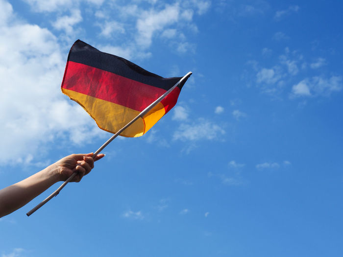 Female hand with the German flag on a summer sky Female Hand German Blue Body Part Cloud - Sky Day Environment Finger Flag Germany Hand Holding Human Body Part Human Hand Human Limb Leisure Activity Lifestyles Low Angle View Nature One Person Outdoors Real People Sky Unrecognizable Person Wind