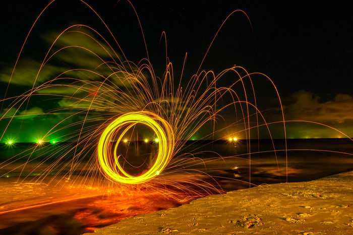 steel wool on the beach look like smiling face Night Motion Illuminated Long Exposure Wire Wool Blurred Motion Glowing Spinning Circle Nature Speed Geometric Shape Outdoors Light Trail Sparks Steel Wool, Fire Work, Heart Shape Smile Angray Light - Natural Phenomenon Shape Pattern Light Painting No People Creativity Light