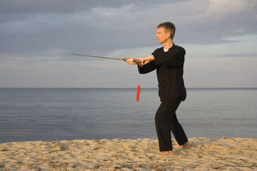 tai chi - posture sweep left - art of self-defense Beach Fitness Full Length Healthy Lifestyle Holding Man Martial Arts Men Nature One Man Only One Mature Man Only One Person Outdoors Sea Self-Defense Forces Selfdefense Side View Sports Clothing Sword Sword Form Tai Chi Tai Chi Chuan Taiji Taijiquan Weapon