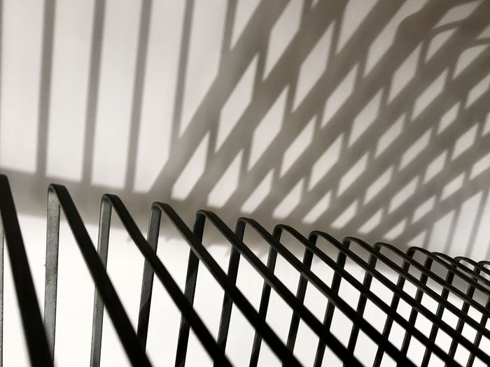Close-up of shadow on railing against wall