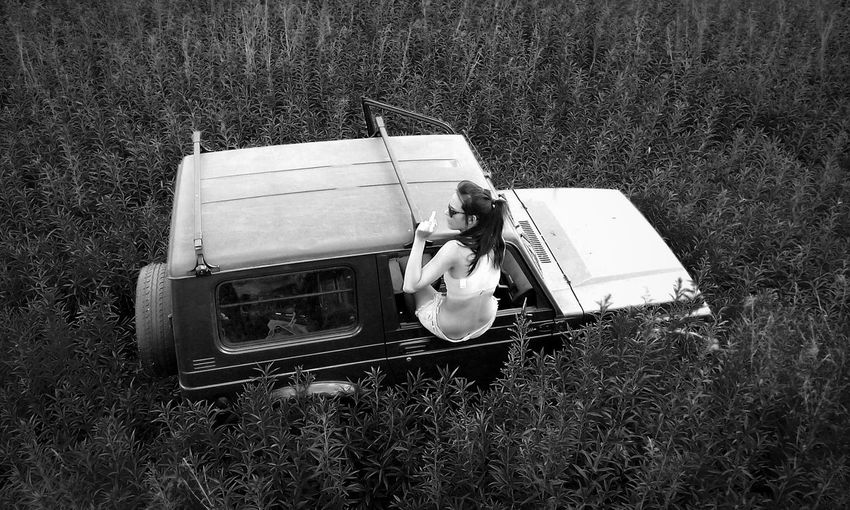 High Angle View Of Young Woman In 4x4 Window In Field