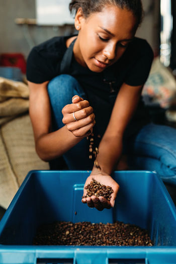 Woman pouring coffee beans in container