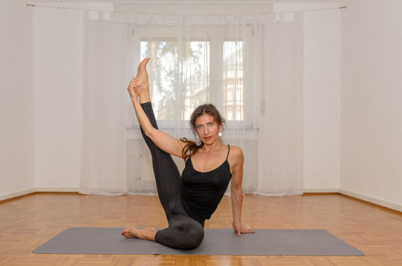 Portrait of mature woman practicing yoga at home