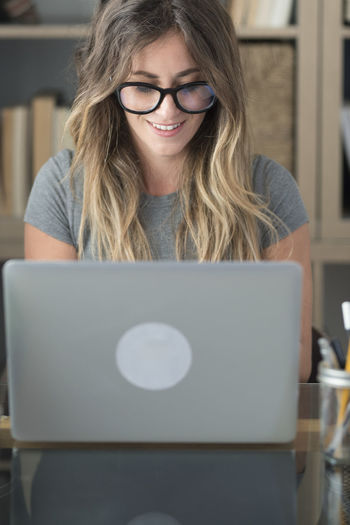 Portrait of smiling young woman using laptop