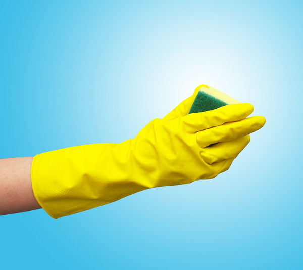 Cropped Hand Wearing Yellow Glove Against Blue Background