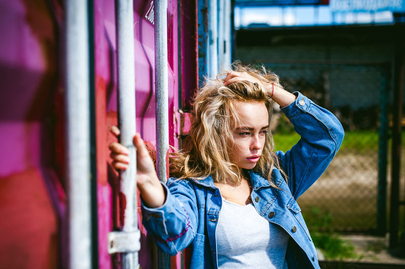 young beautiful woman in jeans clothes outdoors. portrait stylish girl on a freight containers background, on a sunny summer day. Adult Blond Hair Casual Clothing Day Denim Jacket One Person Outdoors People Real People Standing Young Adult Young Women