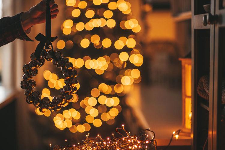 Close-up of hand holding illuminated christmas lights at night