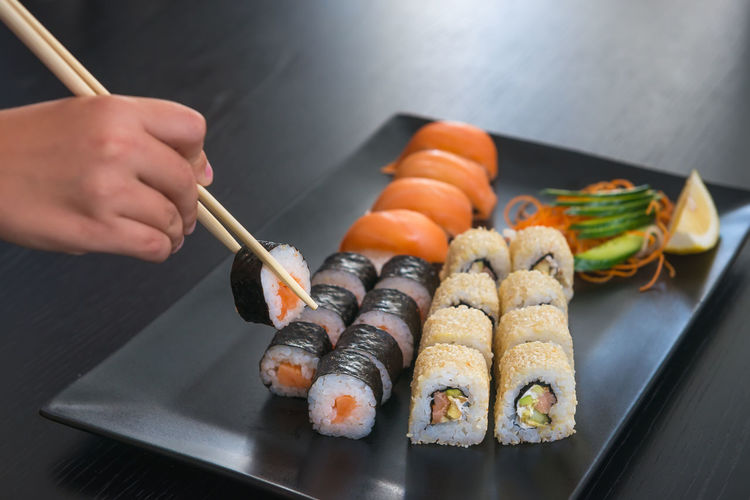 Asian Food Chopsticks Food Food And Drink Freshness Hand Healthy Eating Holding Human Body Part Human Hand Indoors  Japanese Food One Person Preparation  Preparing Food Real People Rice Seafood Sushi Tray Wellbeing