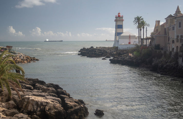 scenic view of sea and buildings against sky Architecture Beauty In Nature Building Building Exterior Built Structure Direction Guidance Horizon Over Water Land Lighthouse Nature No People Outdoors Rock Rock - Object Scenics - Nature Sea Sky Solid Tower Water