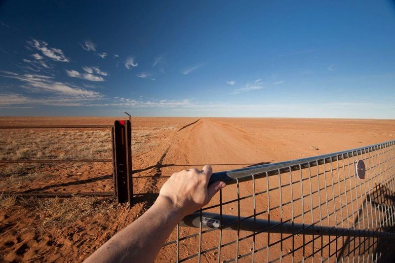 Cropped hand of fence against landscape