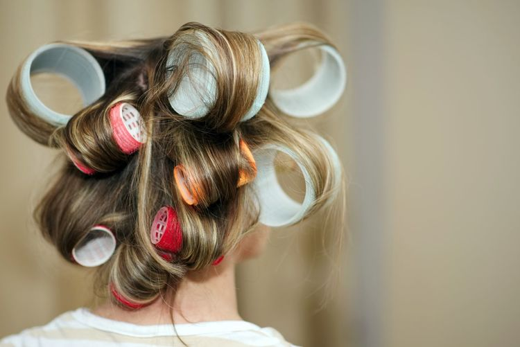 Rear view of woman with hair curlers at salon