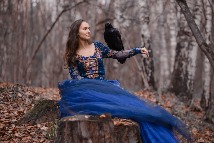 Woman holding bird while sitting at forest