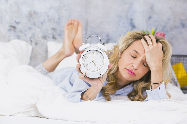 Woman with alarm clock lying on bed against wall at home