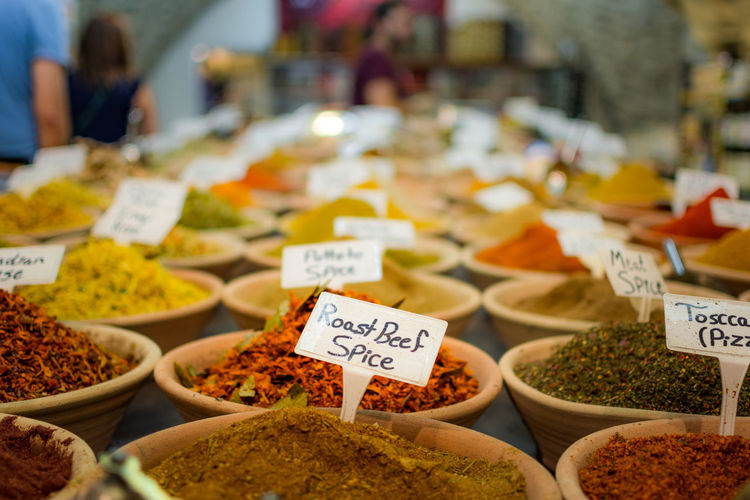 Close-up of spices with labels in bowls for sale at store