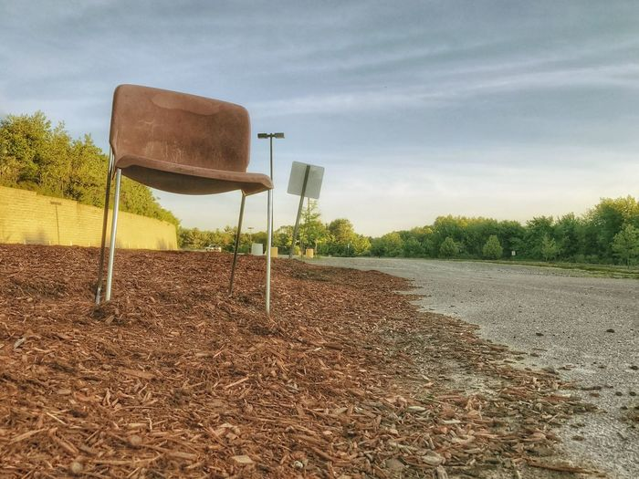 An empty chair and empty parking lot await the return of an attendant and vehicles. Exit Enter Seat Sunset Vacant Parking Lot Wide Open Spaces Furniture Empty Chair Empty Places Chair Beauty In Nature Landscape Scenics Outdoors Cloud - Sky Day Nature No People Sky Tree Low Angle