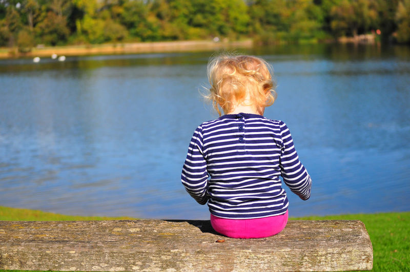Rear view of girl sitting on bench by lake