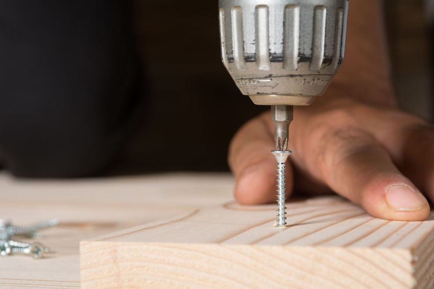 Craftsman working with an electric screwdriver, close up Hand Working Holding Electric Screwdriver Screw DIY Do It Yourself Fixing Wood Repair Craftsman Handyman Craft Assembling Occupation Carpenter Constructing Drilling Home Installation Industry Timber Renovation Skill