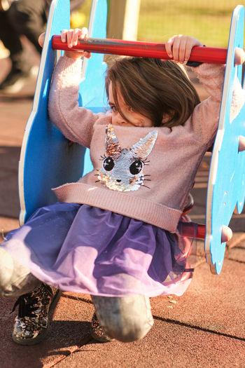 Full length of girl sitting on slide at playground