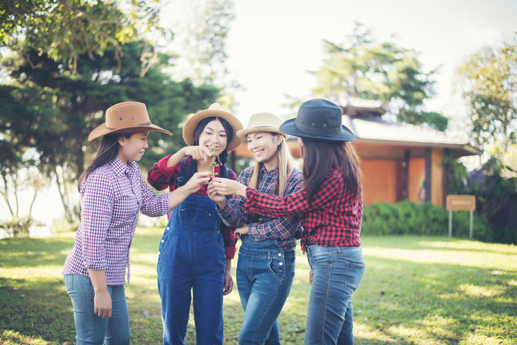Adult Bonding Casual Clothing Day Emotion Friendship Group Of People Hat Holding Leisure Activity Lifestyles Men Outdoors Plant Real People Standing Three Quarter Length Togetherness Tree Women Young Adult